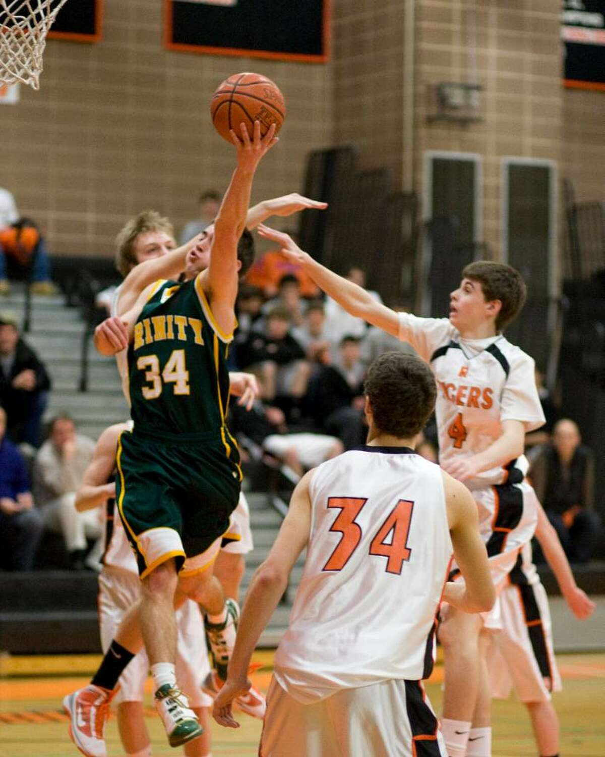 Trinity Catholic's Remy Pinson (34) goes in for a layup in an FCIAC game against Ridgefield Monday night at Ridgefield High.