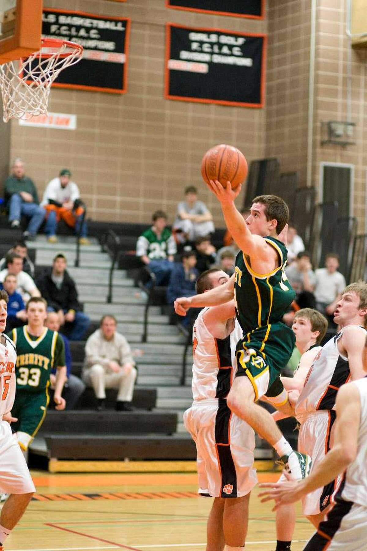 Trinity Catholics's Remy Pinson drives in for a layup during an FCIAC game against Ridgefield Monday night at Ridgefield High.