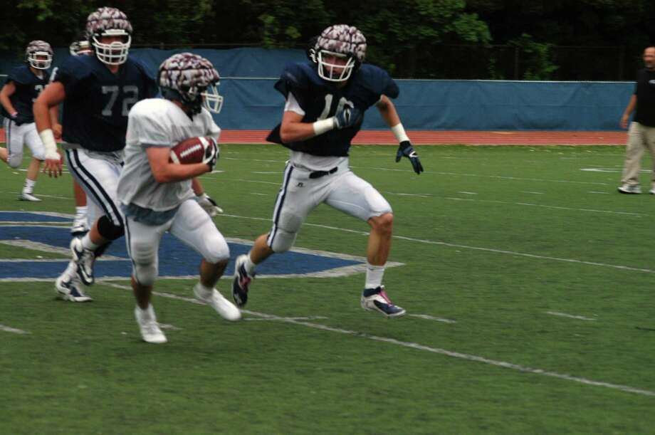 Staples Charles Lomanto carryies the ball as Jackson Ward (72) and Nick Esposito (16) defend during the Wreckers' spring game held June 12. Photo: Andy Hutchison/For The Westport / Westport News Contributed