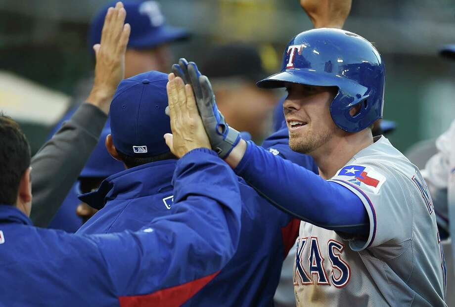 OAKLAND, CA - JUNE 16:  Donnie Murphy #16 of the Texas Rangers is congratulated by teammates after hitting a two-run homer in the top of the fourth inning against the Oakland Athletics at O.co Coliseum on June 16, 2014 in Oakland, California. Photo: Thearon W. Henderson, Getty Images / 2014 Getty Images