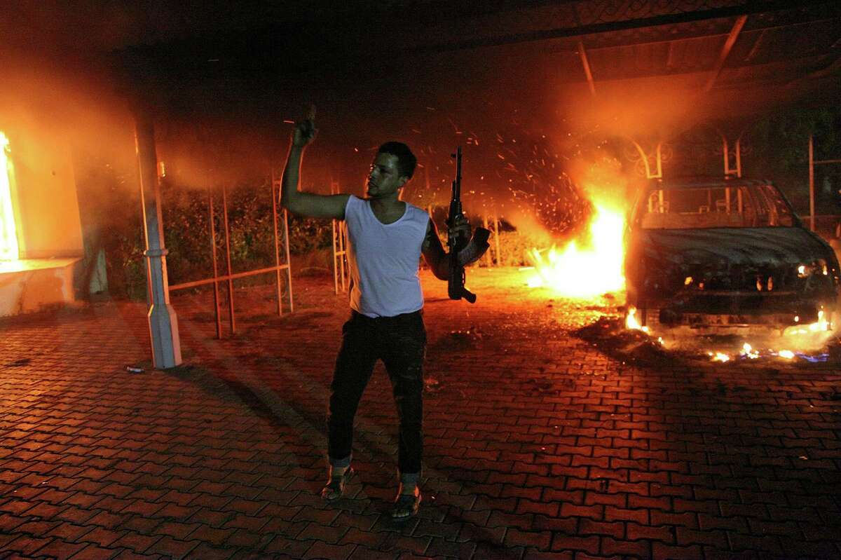 An armed man waves his rifle as buildings and cars are engulfed in flames after being set on fire inside the US consulate compound in Benghazi late on Tuesday. An armed mob protesting over a film they said offended Islam, attacked the US consulate in Benghazi and killed the US ambassador and three other Americans. (STR/AFP/GettyImages)