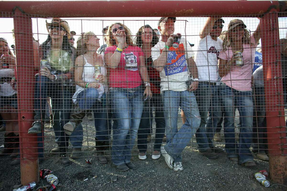 Spectators watch from the beer garden during the 27th annual Lind Lions Club Combine Demolition Derby.