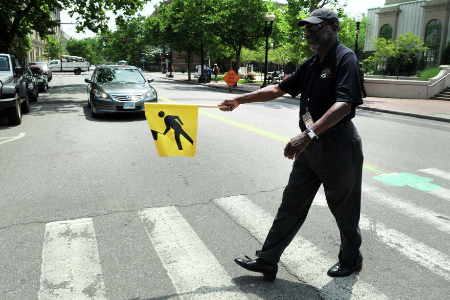 City Councilman James Halloway crosses Broad Street, in downtown Bridgeport, using one of the new cross walk flags he introduced to promote pedestrian safety in the city, June 17, 2017. Photo: Ned Gerard / Connecticut Post