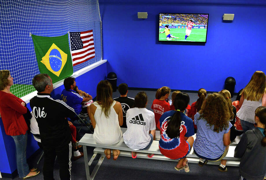 Girls from several U13 FUSA (Fairfield United Soccer Association) soccer teams watch as Brazil plays against Croatia, during a during a World Cup Soccer party held at the new soccer school 'Ole Soccer in Fairfield, Conn. on Thursday June 12, 2014. Photo: Christian Abraham / Connecticut Post