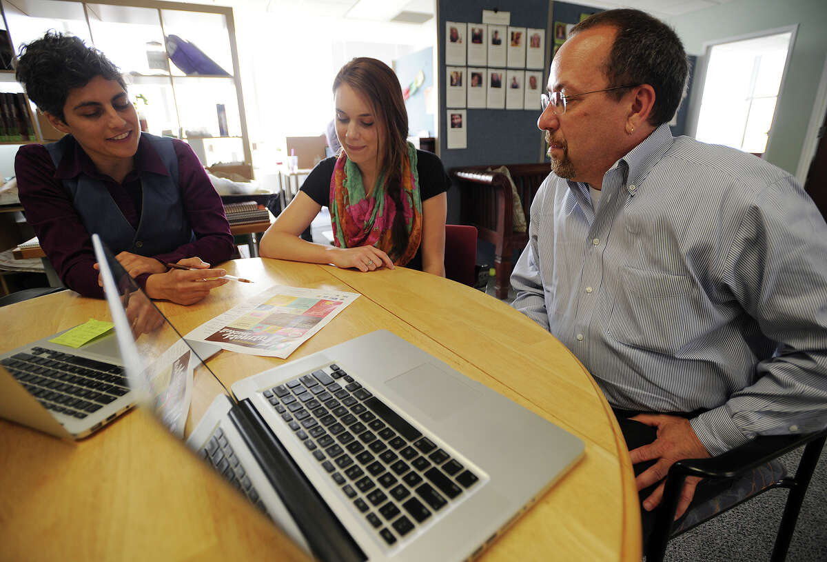 From left; Wholesome Wave's Cristina Sandolo and Leah Johnson discuss a company project with Encore! Hartford intern Harold Topper, of Stamford, Conn., in the non-profit business' offices in Bridgeport, Conn. on Tuesday, June 17, 2014. The UCONN program targets corporate professionals looking to transition to work in the non-profit sector.