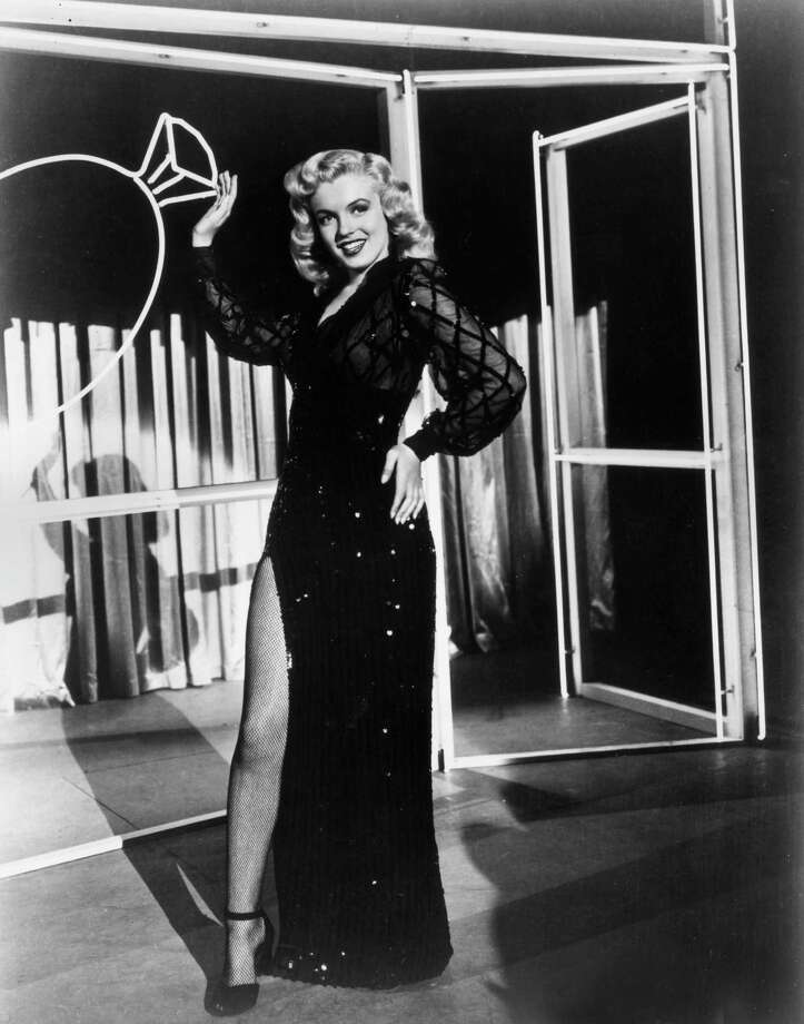 1949Full-length portrait of American actor Marilyn Monroe (1926-1962) wearing an evening dress with a high slit revealing a fishnet stocking, standing in front of a neon-lit set with an image of a diamond ring in a still from director Phil Karlson's film, 'Ladies of the Chorus'. Photo: Hulton Archive, Getty / Archive Photos