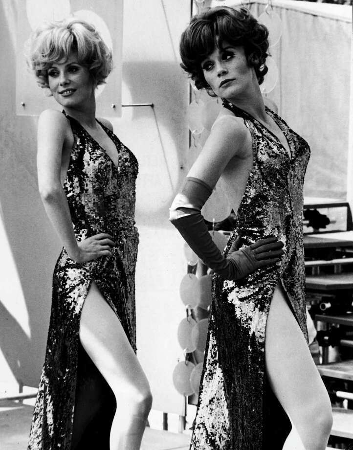 1967French actors Catherine Deneuve and her sister Francoise Dorleac (1942 - 1967) perform a musical number, wearing slit gowns in a scene from the film Les Demoiselles de Rochefort (The Young Girls of Rochefort) directed by Jacques Demy. Photo: Warner Bros., Getty / Moviepix