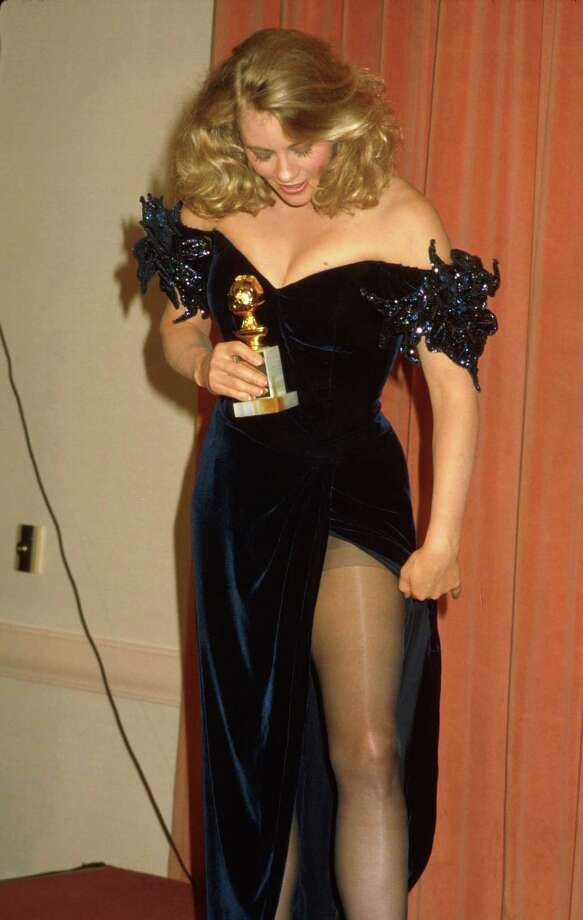 1986Actress Cybill Shepherd, holding her award and showing off slit in left leg of her gown, in Press Room at Golden Globe Awards. Photo: Kevin Winter, Getty / Time Life Pictures