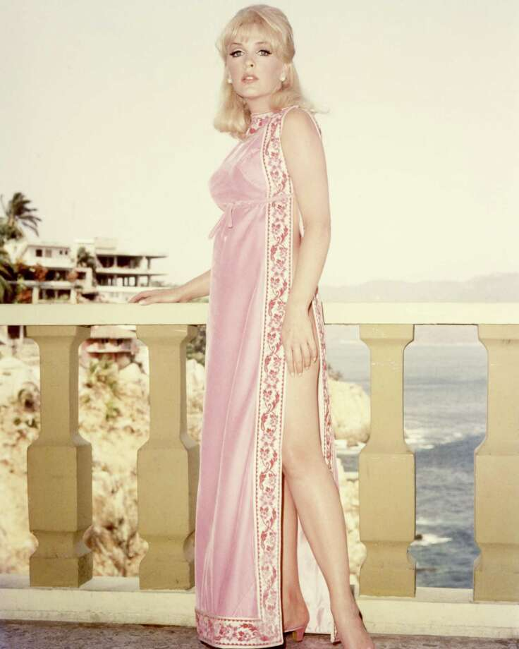 1960Full length shot of Stella Stevens, US actress, wearing a pink silk dress, with her left leg exposed through a split in the skirt, as she poses leaning on a balustrade. Photo: Silver Screen Collection, Getty / Moviepix