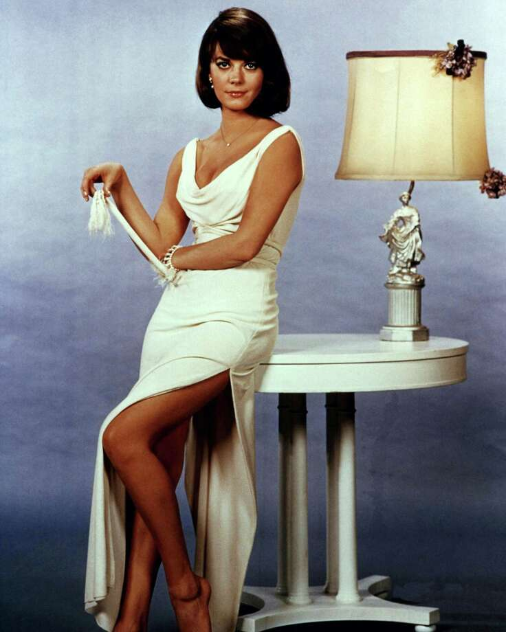 1965Full length portrait of Natalie Wood (1938-1981), US actress, wearing a sleeveless white low cut dress, with her left leg exposed through the split in the skirt, posing beside a white table on which sits table lamp with a cream lampshade. Photo: Silver Screen Collection, Getty / Moviepix
