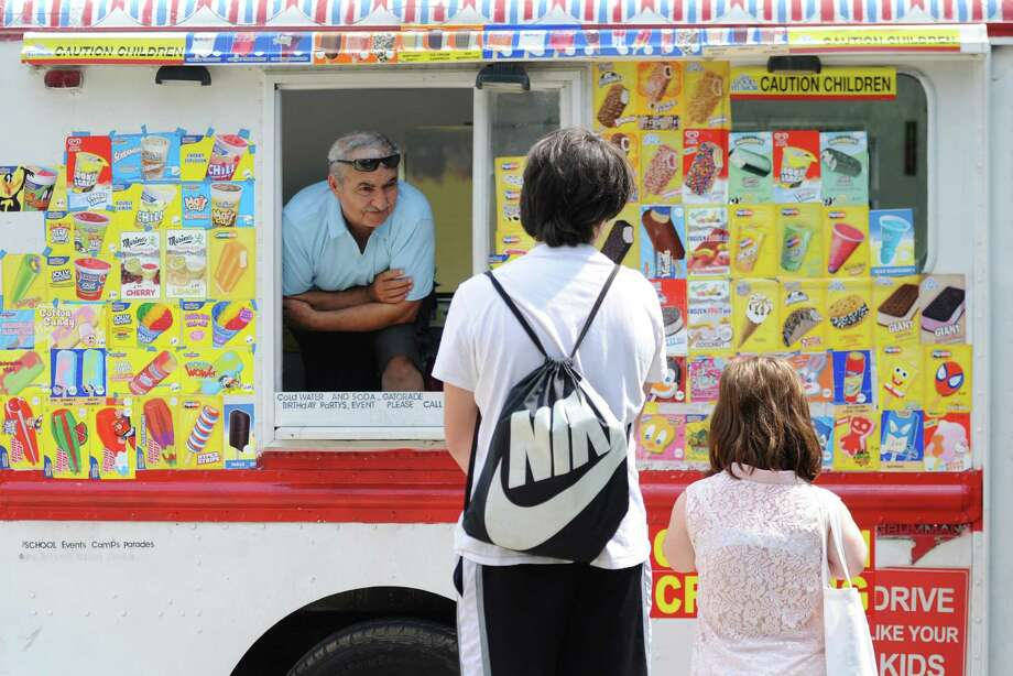 Gamze Ceylan, left, sells ice cream to Aedan Julian, 14, and Natalie Whitton, 15, of Ridgefield, in his ice cream truck outside of Ballard Park in Ridgefield, Conn. Tuesday, June 17, 2014.  Area temperatures rose into the mid-80s and the heat is expected to continue Wednesday. Photo: Tyler Sizemore / The News-Times