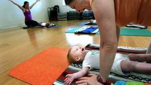 Levitt Gregory, 4, participates with his mother, Heather Doty, during Mommy Baby Yoga at Evergreen Yoga on Monday, June 16, 2014, in Memphis, Tenn.