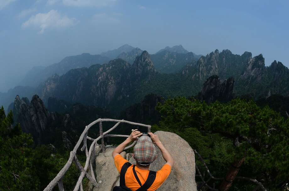 TOPSHOTS This photo taken on June 15, 2014 shows a tourist viewing granite rock formations at Lion Peak in the Huangshan (Yellow Mountains) park in Anhui Province.  The UNESCO World Heritage Site is one of China's major tourist destinations and has been a source of inspiration to Chinese painters, writers and poets for thousands of years.      AFP PHOTO/Mark RALSTONMARK RALSTON/AFP/Getty Images Photo: Mark Ralston, AFP/Getty Images