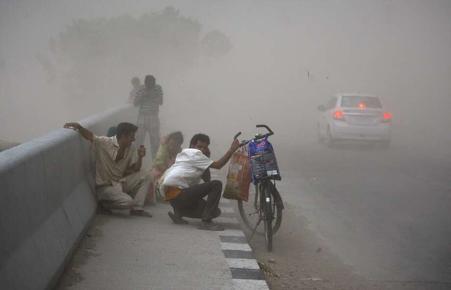 Commuters take cover against blowing sand during a 