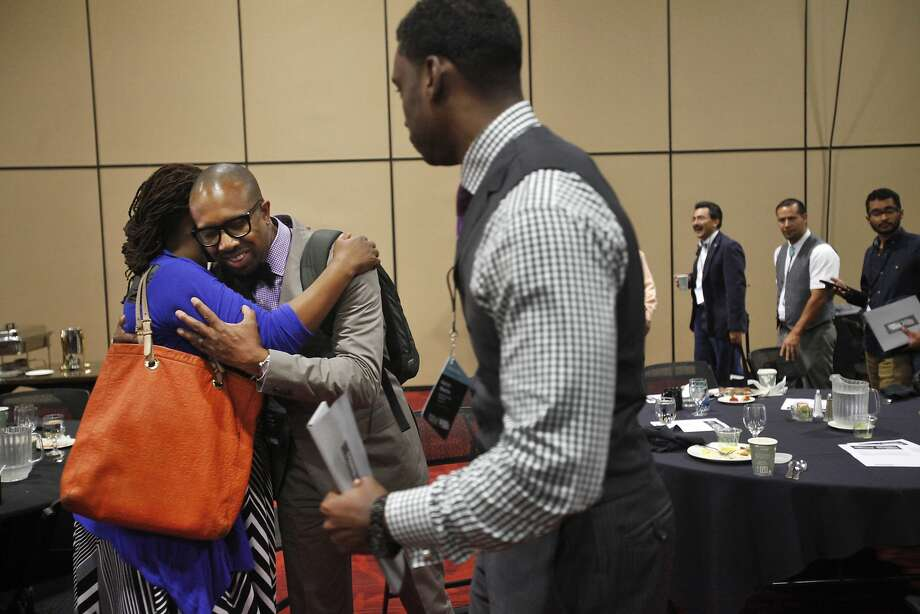 Kisha Bird gives Steve Vassor a hug while he chats with fellow mentor Aaron Martin at the event in Oakland. Photo: Leah Millis, The Chronicle