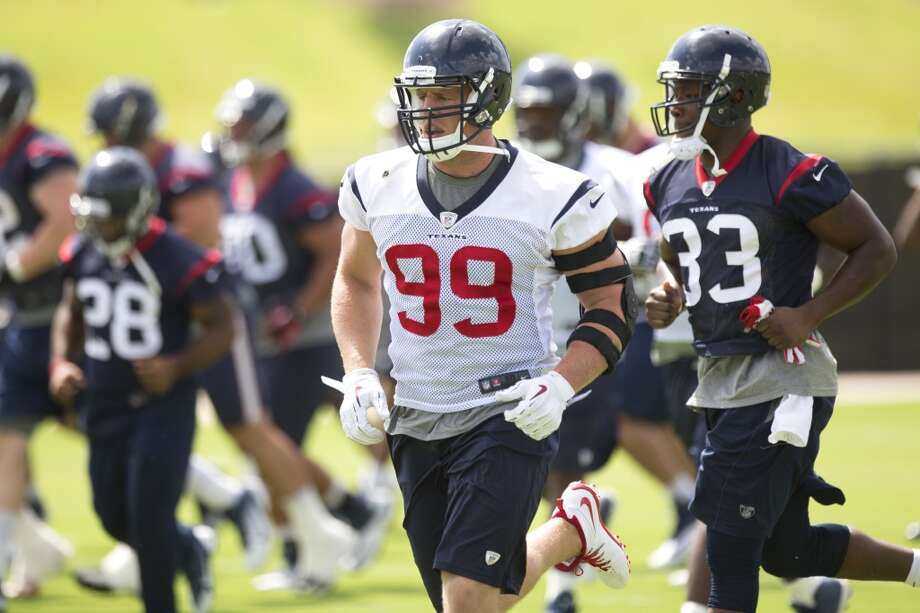 June 17 Texans defensive end J.J. Watt (99) runs with running back Andre Brown (33) during Texans' minicamp at the Methodist Training Center on Tuesday. Photo: Brett Coomer, Houston Chronicle