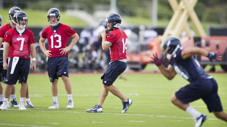Texans quarterback Ryan Fitzpatrick (14) drops back to pass as Case Keenum (7) and T.J. Yates (13) look on. Photo: Brett Coomer, Houston Chronicle