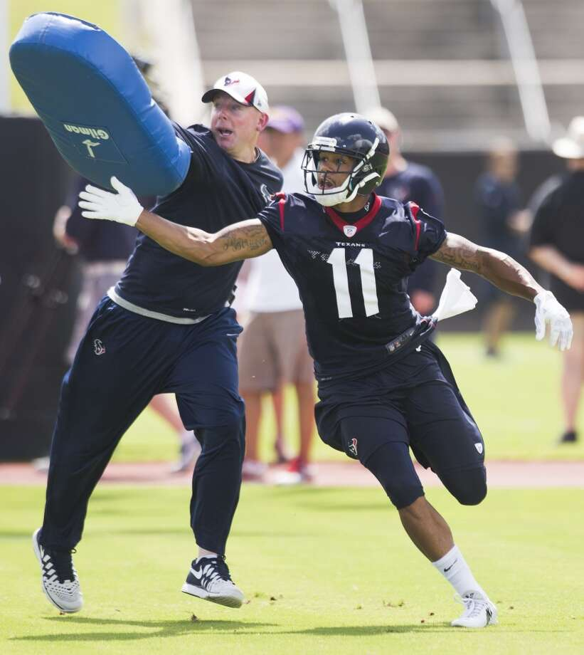 Texans wide receiver DeVier Posey (11) pushes a blocking pad, held by quarterbacks coach George Godsey. Photo: Brett Coomer, Houston Chronicle