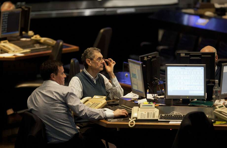 Workers at the Buenos Aires Stock Exchange keep tabs on market fluctuations a day after President Cristina Fernandez's defiant speech. Photo: Eduardo Di Baia, Associated Press