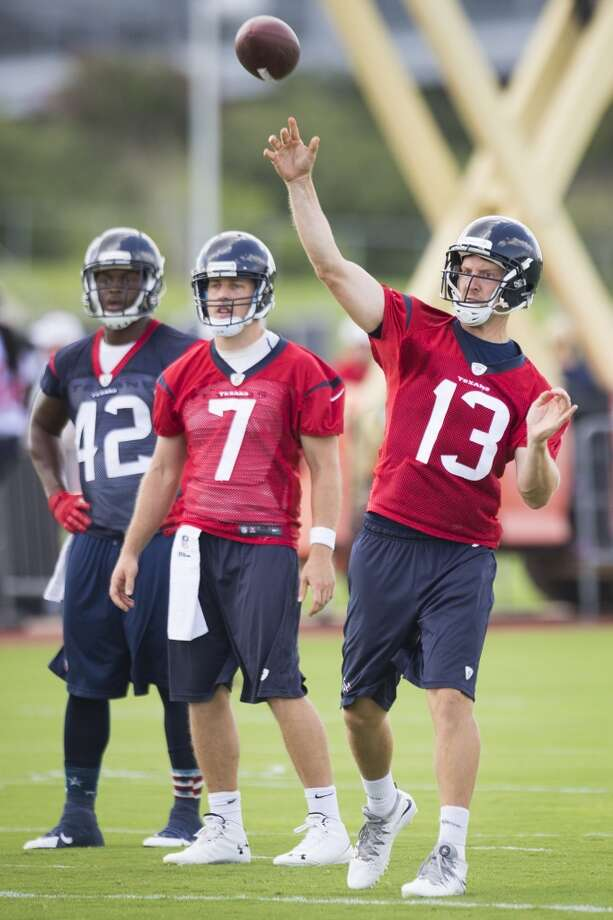 Texans quarterback T.J. Yates (13) throws a pass as running back Toben Opurum (42) and quarterback Case Keenum (7) look on. Photo: Brett Coomer, Houston Chronicle