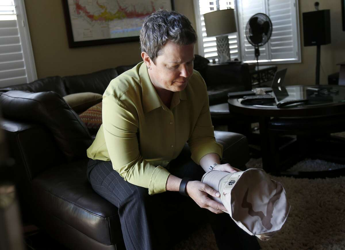Iraq War veteran Kelly McFarland talks about her experiences as she holds her old Navy service hat in her Livermore, Calif home Tuesday June 17, 2014. Kelly McFarland, a veteran of the Iraq War, has been following the recent events in that part of the world with great interest.