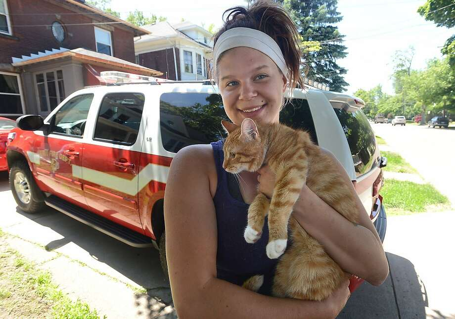 """Cat rescuer has to be rescued as well:When Tara Dennis heard the whimpers of a kitty stuck high up a tree in Erie, Pa., she decided to climb the tree and rescue the feline. Forty feet up, the Good Samaritan reached the tabby and """"put it in my shirt."""" Climbing down while holding a cat proved impossible, however, so local firefighters had to be called to rescue both of them. The owner of the cat has yet to be found. Photo: Jack Hanrahan, Associated Press"""