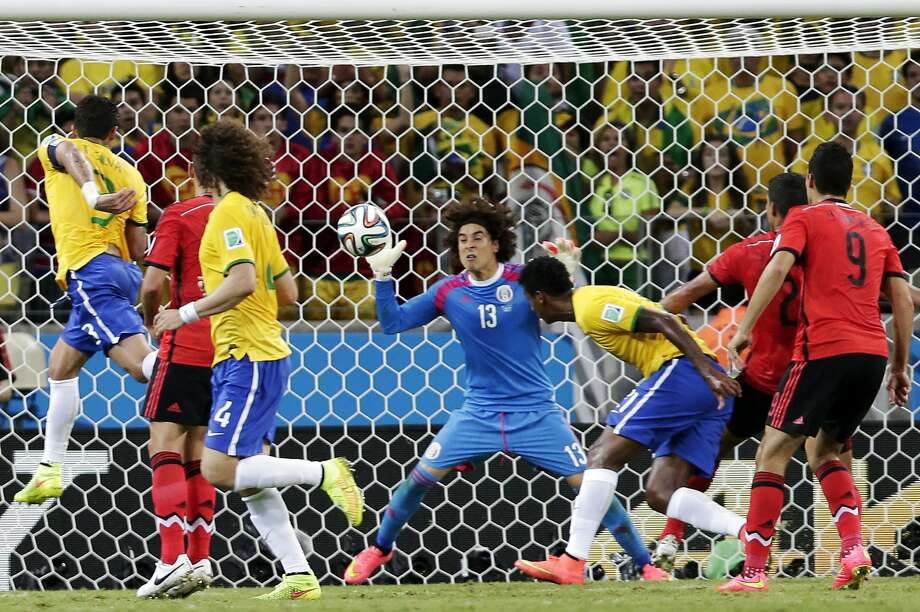 Guillermo Ochoa denies Brazil a goal, batting away a header by Fred. Ochoa's quick reflexes were also on display when he saved Thiago Silva's header at point-blank range in the 86th minute. Photo: Marcio Jose Sanchez, Associated Press