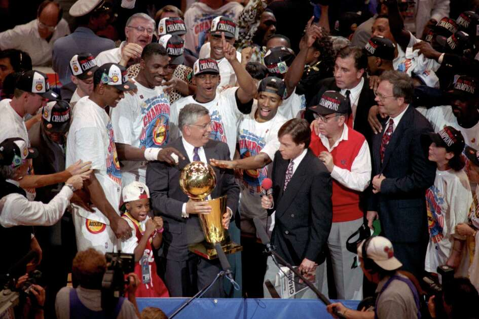 CONTACT FILED: HOUSTON ROCKETS 1994.  06/22/1994 (sheet 62208) - NBA Commissioner David Stern presents the NBA Championship Trophy to the Houston Rockets team after they defeated the New York Knicks in the 7th and final game, June 22, 1994. This frame was used on the Chronicle Rockets Extra, 6/26/94.    Houston Chronicle Photo by Christobal Perez.     HOUCHRON CAPTION (06/13/2004):  THE GANG'S ALL HERE:  Rockets players and coaches crowd around NBA commissioner David Stern, center left, and NBC's Bob Costas for the moment Houston had been waiting for.