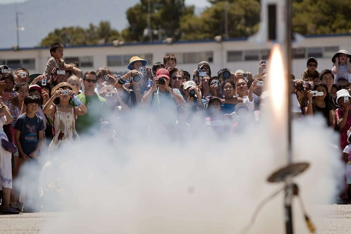 Moonfest attendees watches a scaled model of a Saturn V rocket takes off from the Moffett Federal Field runway during Moonfest in commemoration of the 40th anniversary of the lunar landing during Moonfest held at Ames Research Center in Mountain View, Calif. Sunday, July 19, 2009.