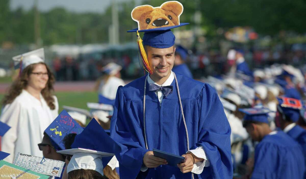 Michael Schneider, 18, walks back to his seat after receiving his diploma during the Danbury High School 2014 Commencement Exercises, held on the high school stadium field on Tuesday, June 17, 2014, in Danbury Conn.