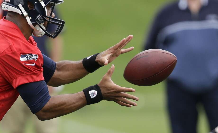 Seattle Seahawks quarterback Russell Wilson reaches for the ball at Seahawks minicamp on Tuesday. Photo: Elaine Thompson, Associated Press