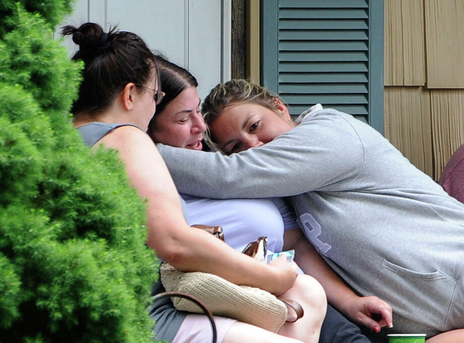 Kerry Gottlieb, center, owner of the home where a small airplane crashed in her backyard that killed the pilot is hugged by friend, Jill Cherveny, right on Tuesday, June 17, 2014, in East Patchogue, N.Y. The plane crashed  in between two houses on the tree-lined working-class street, according to Brookhaven Town spokesman Kevin Molloy.  The Federal Aviation Administration said the aircraft was a single-engine Lancair Columbia with one person was on board. It was flying from Republic Airport in Farmingdale to MacArthur Airport in Islip, the agency said. (AP Photo/Kathy Kmonicek) ORG XMIT: NYKK107 Photo: Kathy Kmonicek / FR170189 AP