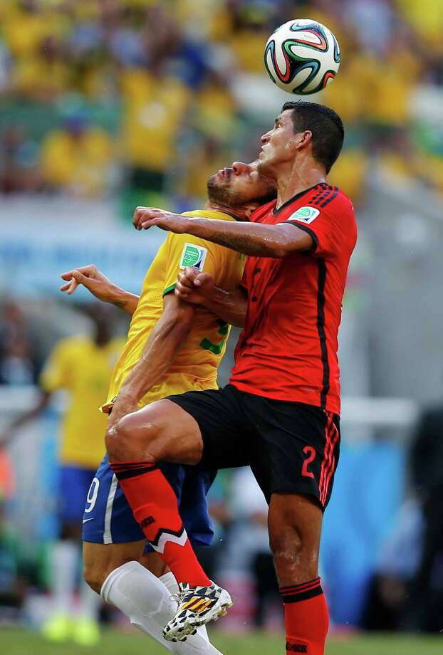 Mexico's Francisco Rodriguez, right, heads the ball against Brazil's Fred during the group A World Cup soccer match between Brazil and Mexico at the Arena Castelao in Fortaleza, Brazil, Tuesday, June 17, 2014.  (AP Photo/Eduardo Verdugo) ORG XMIT: WCDP159 Photo: Eduardo Verdugo / AP