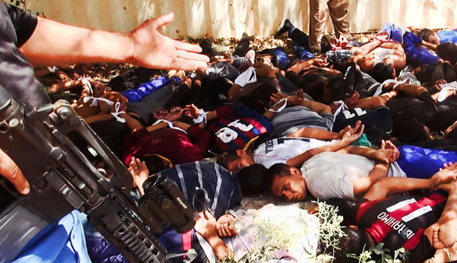A militant website posted this image on Saturday, showing what appears to be militants from an al-Qaida-inspired group with captured Iraqi soldiers after taking over a base in Tikrit, Iraq. Photo: Associated Press / militant website