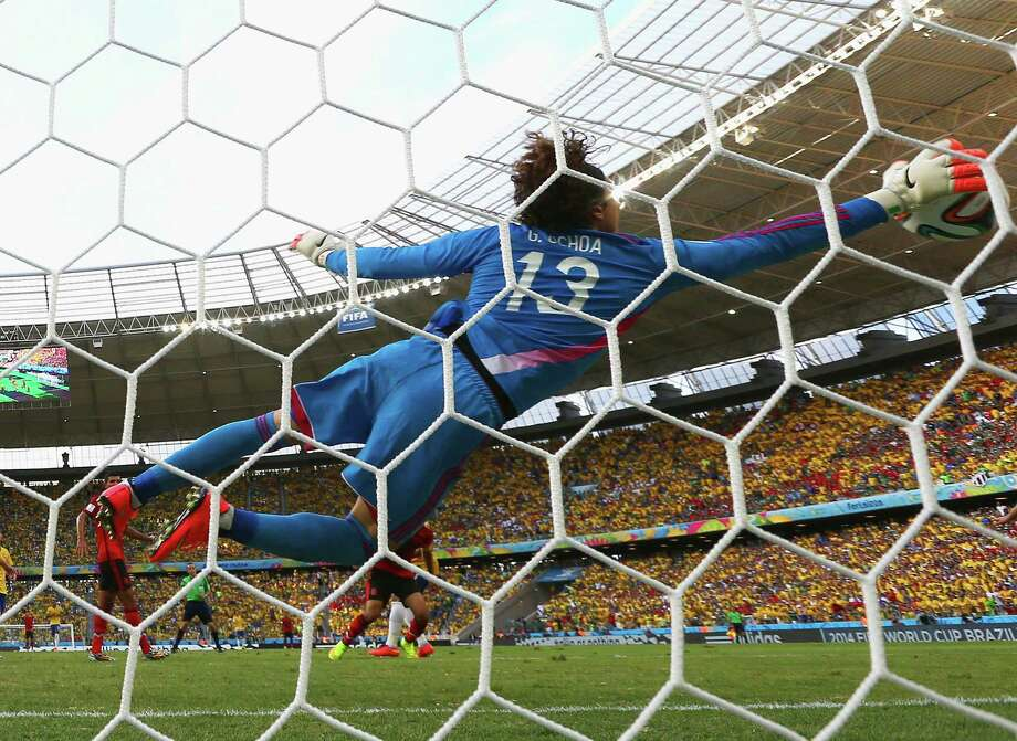 "Mexico goalkeeper Guillermo Ochoa makes a diving save during a 0-0 draw against Brazil. Ochoa made a series of acrobatic stops to preserve the tie. ""It was the match of my life,"" he said. ""To do it in a World Cup, in front of all the fans, it's incredible."" Photo: Robert Cianflone / Getty Images / 2014 Getty Images"