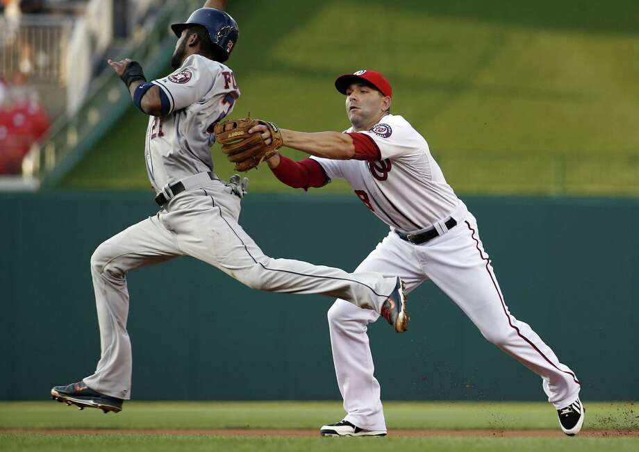 Washington second baseman Danny Espinoza tags out Houston's Dexter Fowler before throwing to first to complete a double play in the first inning of the Nationals' series-opening victory. Photo: Alex Brandon / Associated Press / AP
