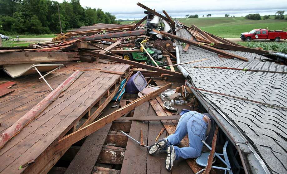 Eric Schroeder reaches for a nearby bow saw in his 90-year-old barn that fell after an early 5 a.m. storm hit the area along County P, east of Clarno, Wis., Tuesday, June 17, 2014. No injuries or death related to the storms had been reported, according to Green County Sheriff Mark Rohloff.  (AP Photo/The Monroe Times, Anthony Wahl) Photo: Anthony Wahl, Associated Press