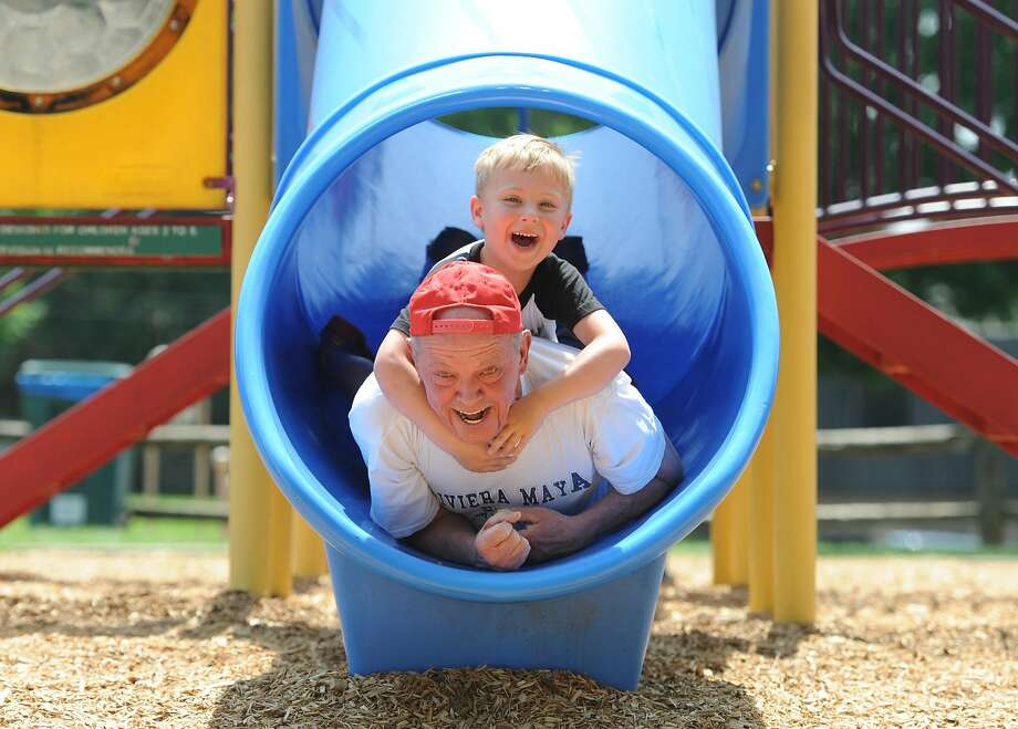 Pat Corbett, 66, and his grandson Chase Bell, 5, Miles Park go down a slide in Whitemarsh, Pa., Tuesday, June 17, 2014. (AP Photo/The Philadelphia Inquirer, Clem Murray) Photo: Clem Murray, Associated Press