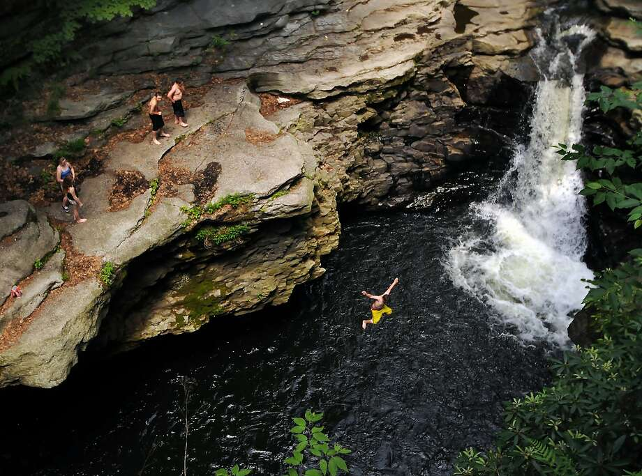 A person leaps off the Nay Aug Park Gorge into Roaring Brook on Tuesday, June 17, 2014, in Scranton, Pa. (AP Photo/Scranton Times & Tribune, Butch Comegys)  WILKES BARRE TIMES-LEADER OUT; MANDATORY CREDIT Photo: Butch Comegys, Associated Press