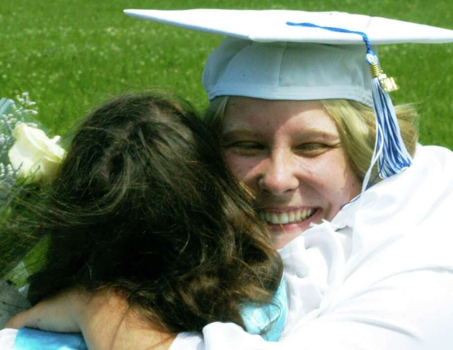 Kim Valentine, right, shares a mutually congratulatory hug with a fellow graduate moments after the Shepaug Valley High School commencement ceremony had been completed, June 14, 2014, on the school campus in Washington. Photo: Norm Cummings / The News-Times