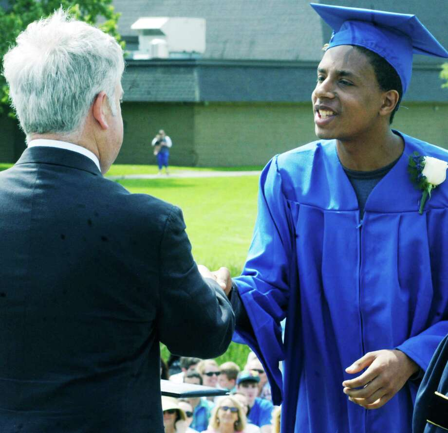Graduate Cameron Cloud accepts the congratulations of Region 12 Board of Education chairman James Hirschfield while being presented his diploma during the Shepaug Valley High School commencement ceremony, Jne 14, 2014, on the school campus in Washington. Photo: Norm Cummings / The News-Times