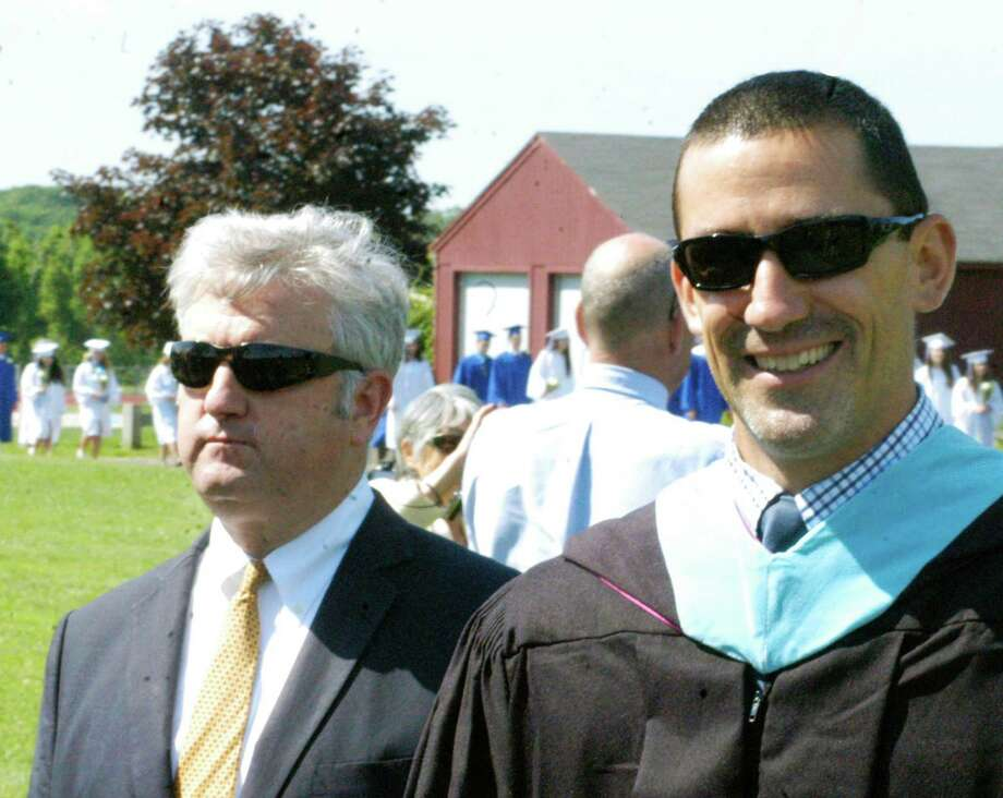 Region 12 Board of Education chairman James Hirschfield maintains a stoic demeanor as he walks alongside the more upbeat Matt Perachi, Shepaug's athletic director and assistant principal, during the processional for the Shepaug Valley High School graduation ceremony, June 14, 2014, on the school campus in Washington. Photo: Norm Cummings / The News-Times