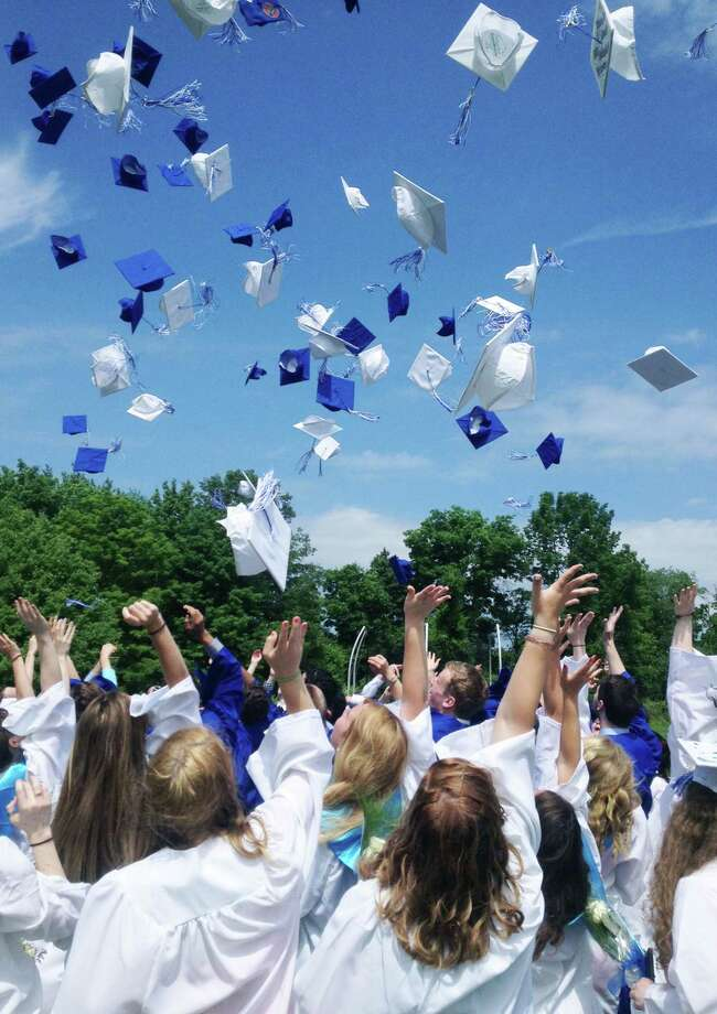 The Shepaug Valley High School Class of 2014 offers an impressive display of a unison toss as their mortarboard hats fly into the deep blue sky moments after the school's commencement ceremony, June 14, 2014, on the campus in Washington. Photo: Norm Cummings / The News-Times