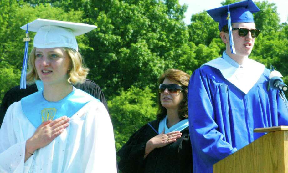 Class valedictorian Clara Wolfe and assistant principal Lori Ferreira join Class of 2014 president Tom McCluskey in the Pledge of Allegiance during the Shepaug Valley High School graduation ceremony, June 14, 2014, on the school campus in Washington. Photo: Norm Cummings / The News-Times