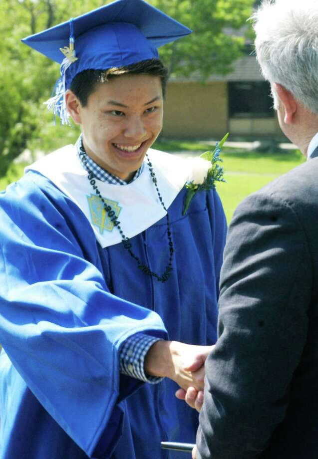 Nathan Ong happily receives his diploma from Region 12 Board of Education chairman James Hirschfield during the Shepaug Valley High School graduation ceremony, June 14, 2014, on the school campus in Washington. Photo: Norm Cummings / The News-Times