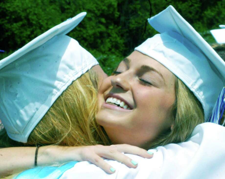 Freshly minted graduate Taylor Weston shares a heartfelt hug with a classmate moments after the Shepaug Valley High School commencement ceremony, Jne 14, 2014, on the school campus in Washington. Photo: Norm Cummings / The News-Times