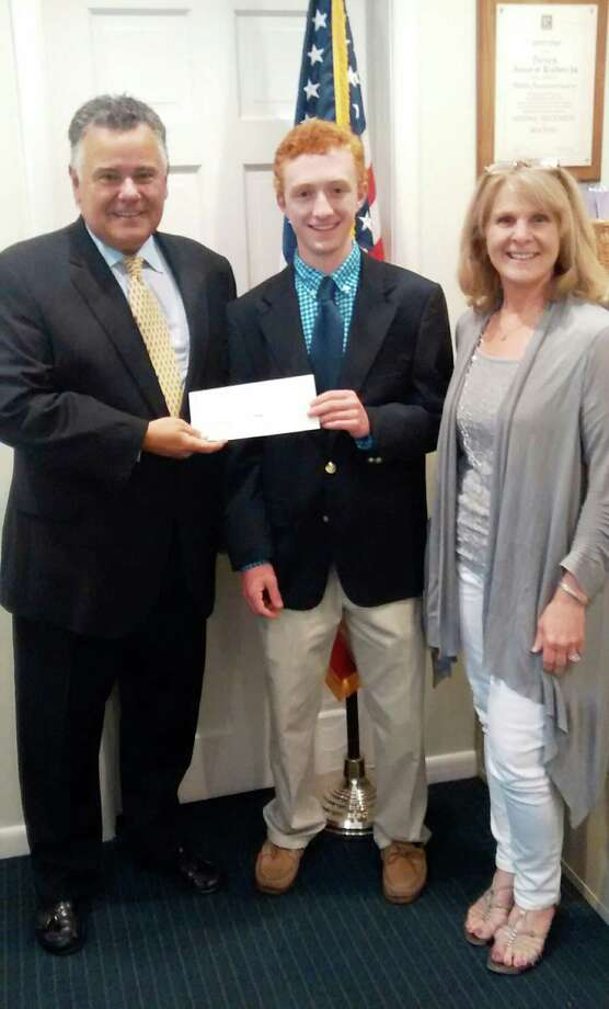 Dave Wilk, left, the present of the Darien Board of Realtors, present at check from the Raymond F. Gates Jr. Memorial Scholarship Fund to Darien High School student Alex Rayhill. With them, Rayhill's mother, Anne Marie Rayhill, a Darien Realtor. Photo: Contributed Photo, Contributed / Darien News