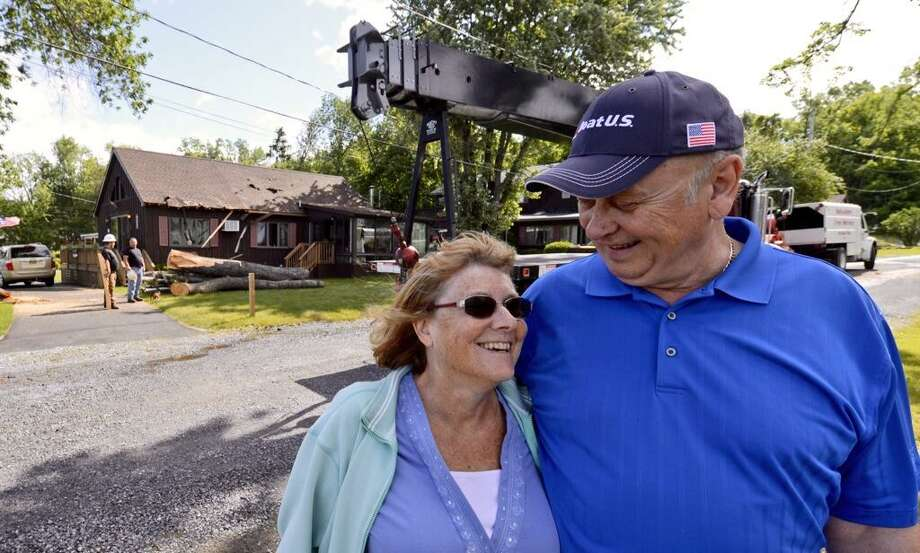 Saying they are lucky to be alive after a tree crashed into their Saratoga Lake house, Caroline and Mike Schleicher can smile on Wednesday. (Skip Dickstein/Times Union)