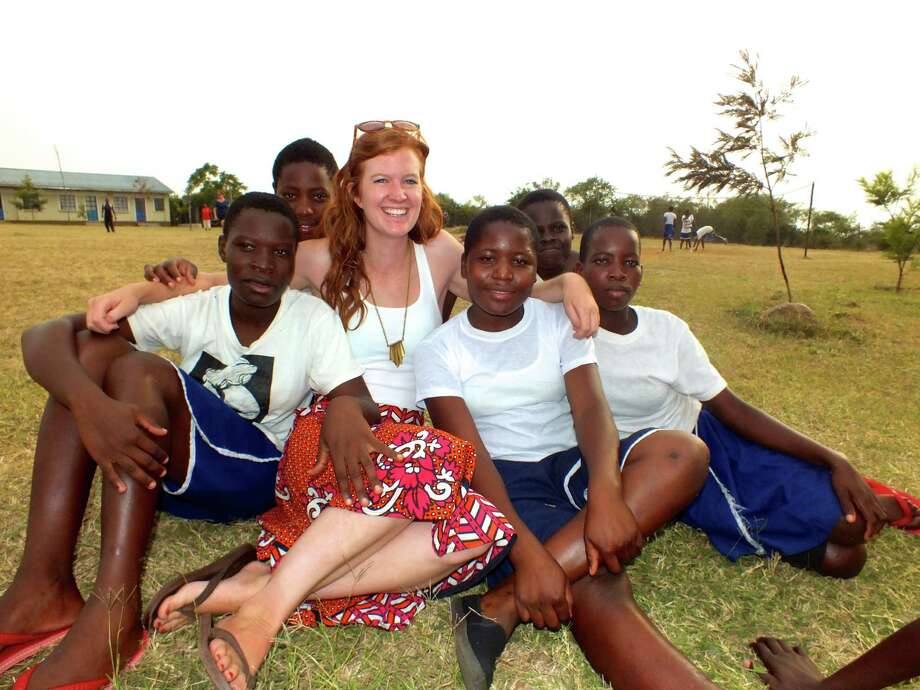 Elizabeth Moran, a New Canaan woman who works with Nairobi-based organization WISER, Women's Institute for Secondary Education and Research, relaxes with a group of students outside a school in Kenya in February 2014. Photo: Contributed Photo, Contributed / New Canaan News Contributed