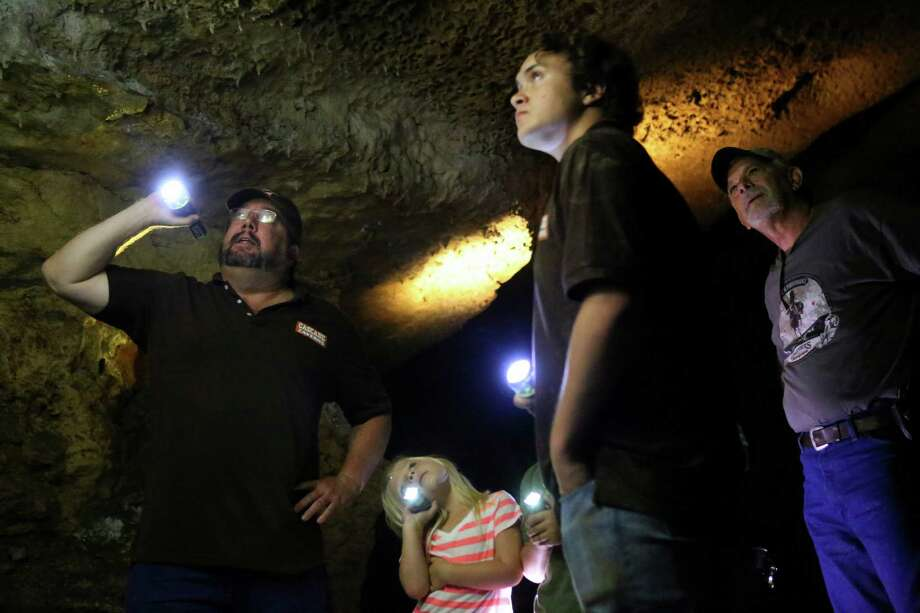 From left, tour guide James Franssen describes a cave formation as Bailey Wells, 6, tour guide Lynnrae Smith and Chuck Wells listen on Tuesday, June 17, 2014, at Cascade Caverns in Boerne, Texas. Photo: Timothy Tai, San Antonio Express-News / © 2014 San Antonio Express-News